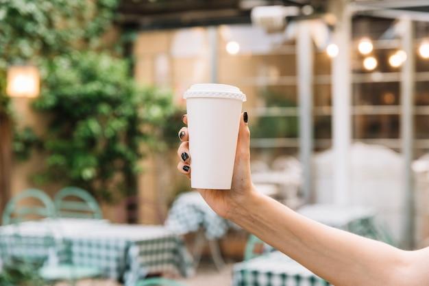 De holding van de hand haalt koffie weg