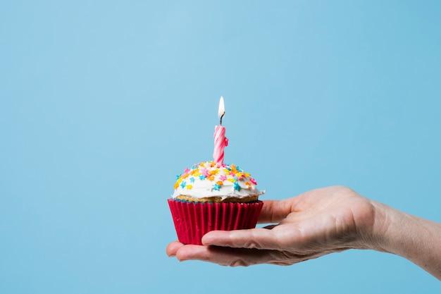De holding van de vooraanzichtpersoon cupcake met aangestoken kaars