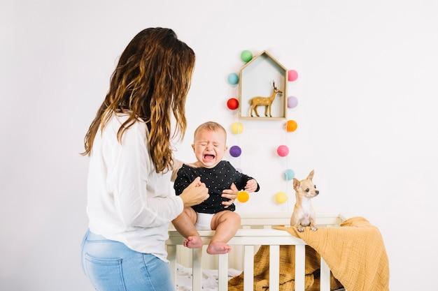 De holdings huilende baby van de vrouw dichtbij hond