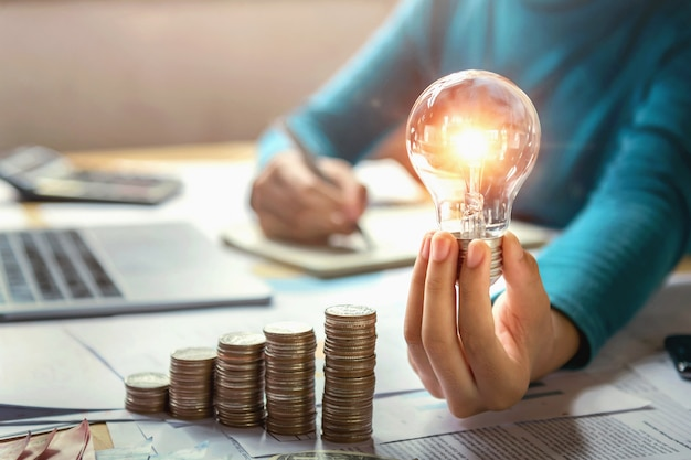 De holdings lightbulb van de bedrijfsvrouwenhand met muntstukkenstapel op bureau. concept dat energie en geld bespaart