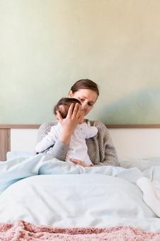 De holdingsbaby van de vrouw in wapens in bed
