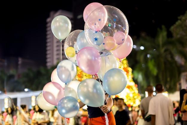 De holdingsballon van de vrouw met verjaardagstekst op het op onduidelijk beeldachtergrond.