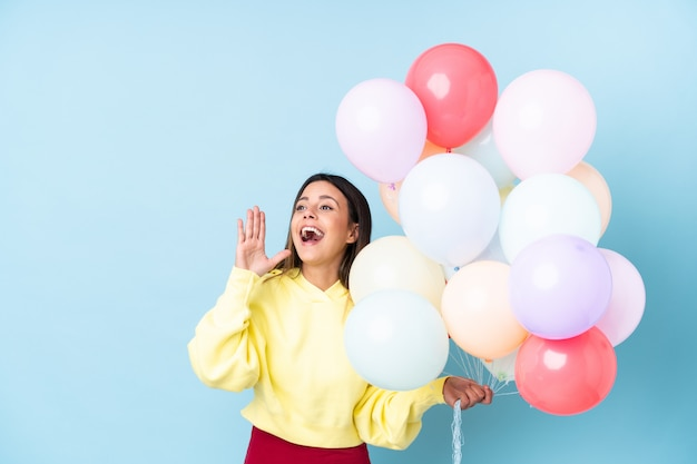 De holdingsballons van de vrouw in een partij over blauwe muur die met wijd open mond schreeuwt