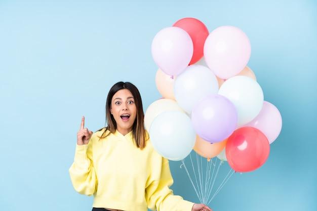 De holdingsballons van de vrouw in een partij over blauwe muur met verrassingsgelaatsuitdrukking