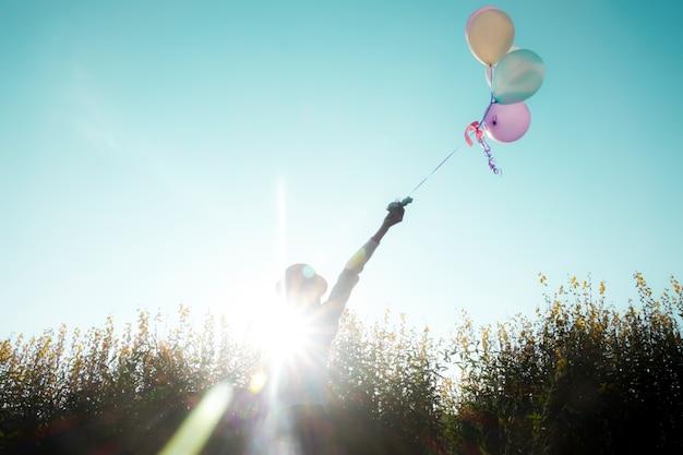 De holdingsballons van het meisje in de zomerdag
