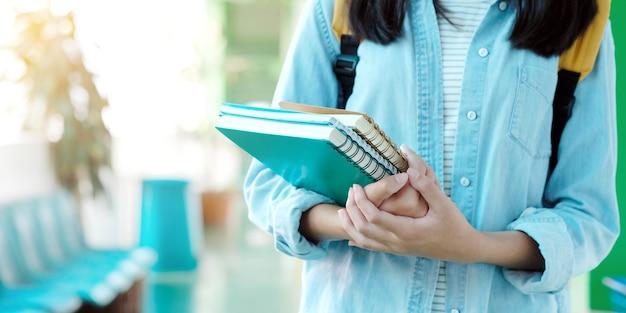 De holdingsboeken van het studentenmeisje en dragen schooltas terwijl het lopen op de achtergrond van de schoolcampus