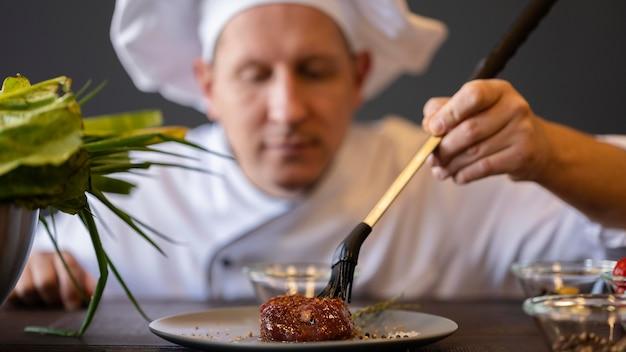 De holdingsborstel van de close-up de wazige chef-kok