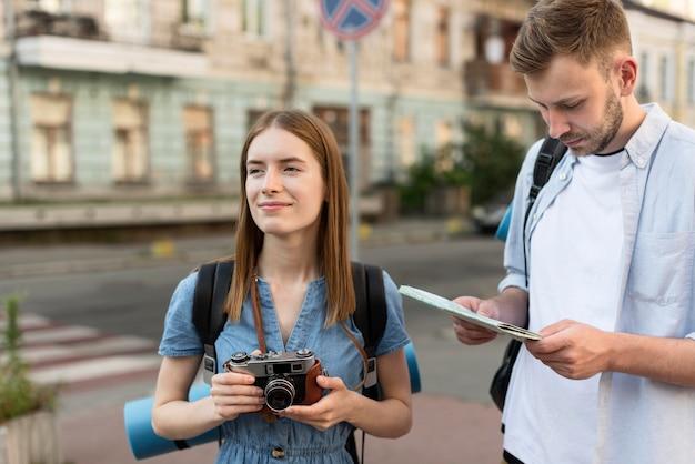 De holdingscamera en kaart van het toeristenpaar