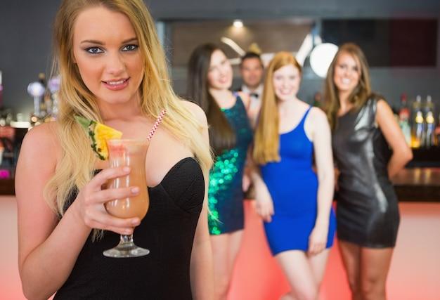 De holdingscocktail die van de blonde aantrekkelijke vrouw zich voor haar vrienden bevinden