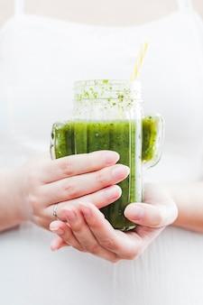 De holdingsfles van de vrouw groene smoothie