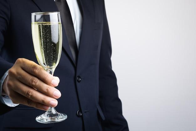 De holdingsglas van de bedrijfsmensenhand champagne voor viering