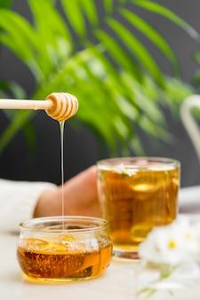De holdingsglas van de vooraanzichtvrouw met thee en honingsdipper