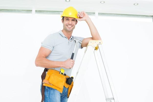 De holdingshamer van de technicus terwijl het dragen van bouwvakker op stapladder
