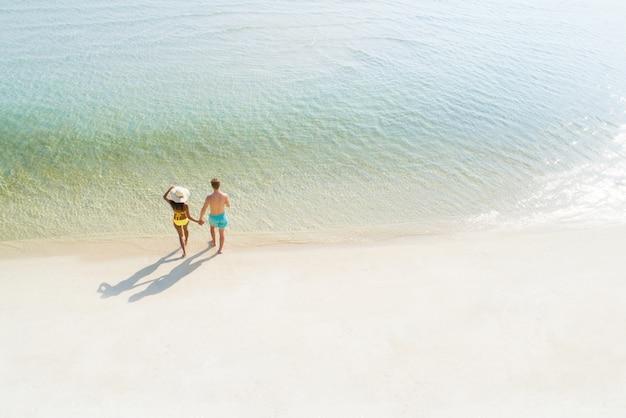 De holdingshand die van het wittebroodswekenpaar op mooi wit zandstrand lopen in de zomer