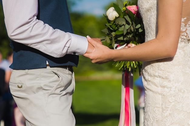 De holdingshand van de bruidegom van zijn bruid