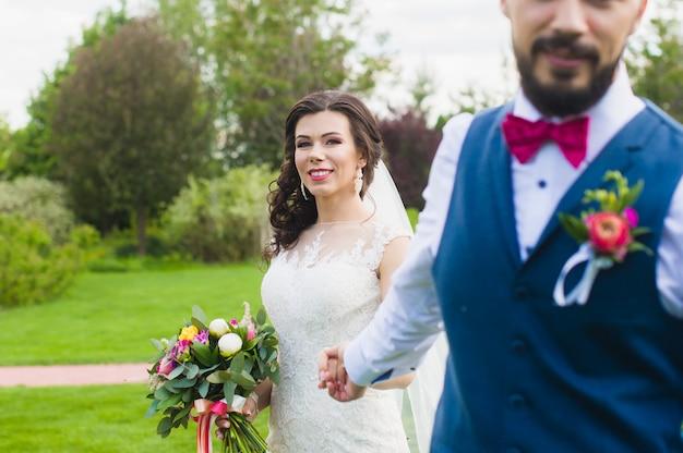 De holdingshand van de bruidegom van zijn glimlachende gelukkige bruid
