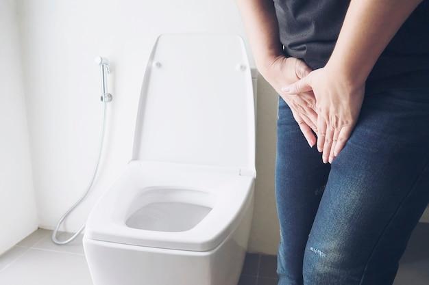 De holdingshand van de vrouw dichtbij toiletkom - het concept van het gezondheidsprobleem