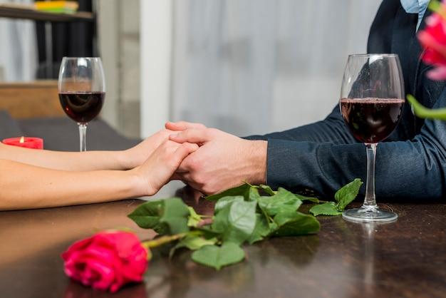 De holdingshanden van de man met vrouw bij lijst met glazen en bloei