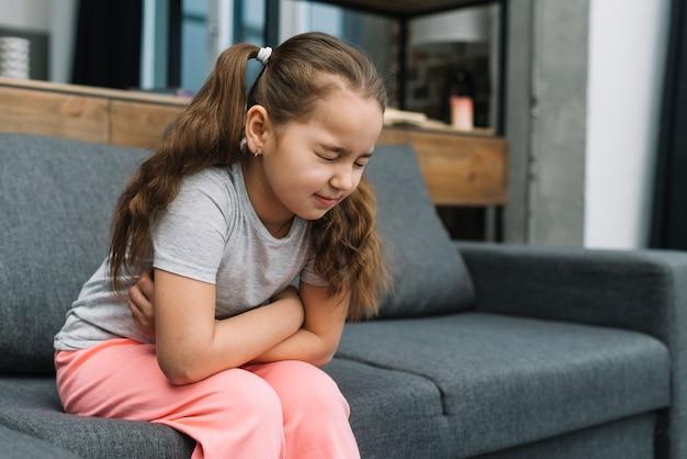 De holdingshanden van het meisje op haar maag die aan pijn lijden
