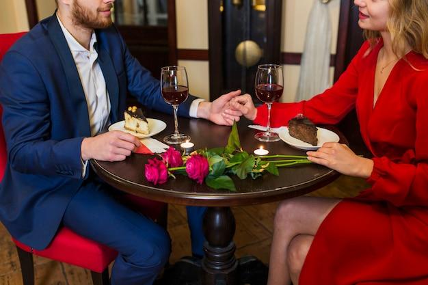De holdingshanden van het paar bij lijst in restaurant