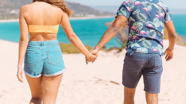 De holdingshanden van het paar en het kijken op zee