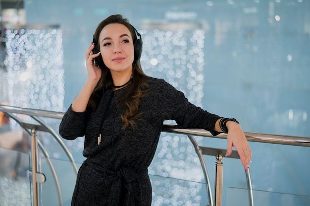De holdingshoofdtelefoons van de vrouw op hoofd in winkelcomplex
