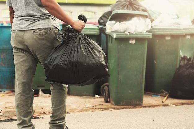 De holdingshuisvuil van de vrouwenhand in zwarte zak voor binnen het schoonmaken aan afval