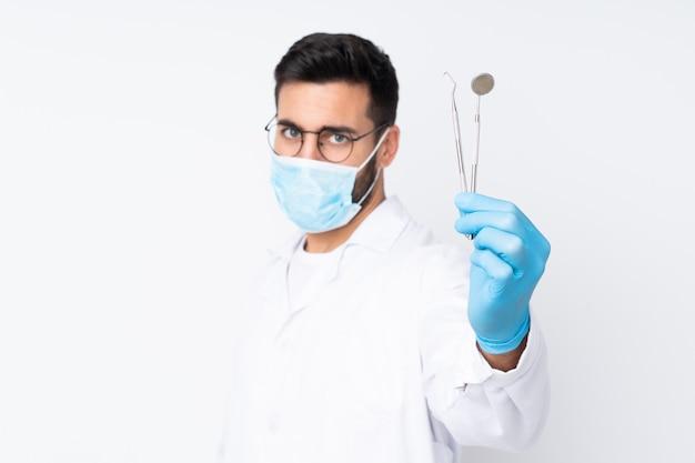 De holdingshulpmiddelen van de tandartermens op witte muur