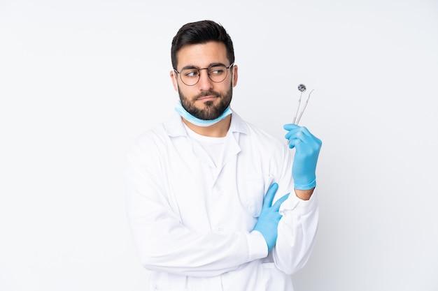 De holdingshulpmiddelen van de tandartsmens die op witte muur worden geïsoleerd die een idee denken