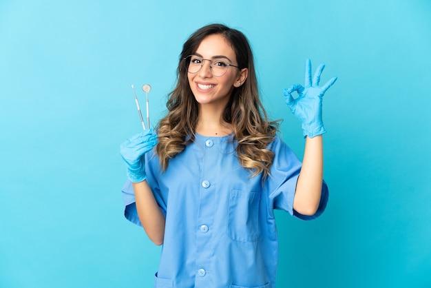De holdingshulpmiddelen van de vrouwentandarts over geïsoleerd op blauwe achtergrond die ok teken met vingers tonen