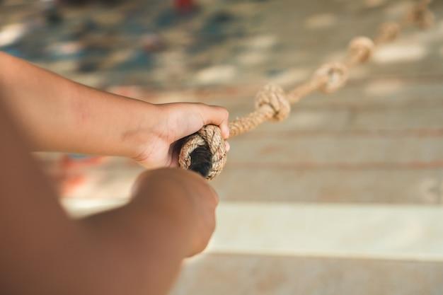 De holdingskabel van de kindhand terwijl het beklimmen van een houten muur in de speelplaats