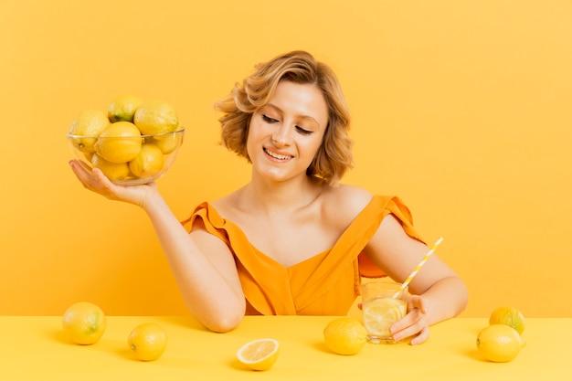 De holdingskom van de smileyvrouw met citroenen