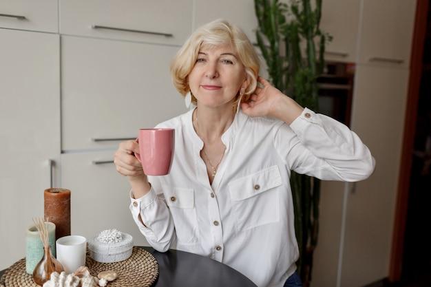 De holdingskop thee van de blondevrouw en het zitten bij moderne keuken