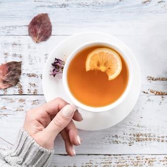 De holdingskop thee van de gewassenvrouw op sjofele oppervlakte