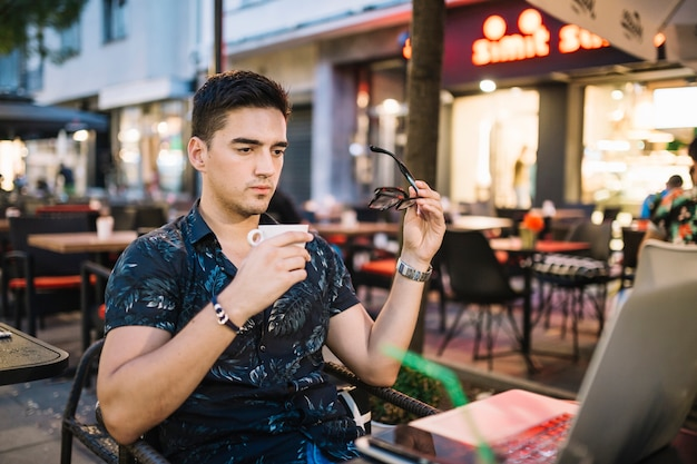 De holdingskop van de mens koffie die laptop in caf� bekijkt