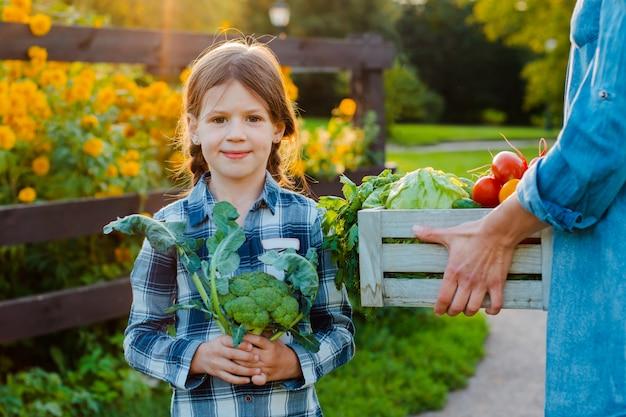 De holdingsmamma van het kinderenmeisje een mand verse organische groenten met de huistuin.
