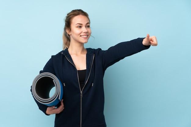 De holdingsmat van het tiener russisch meisje die op blauw wordt geïsoleerd dat een duim omhoog gebaar geeft