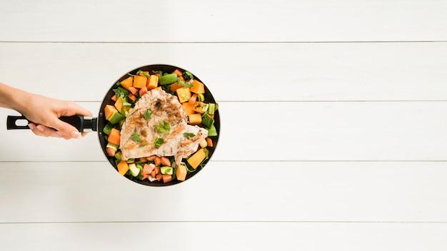 De holdingspan van de persoon met vlees en groenten