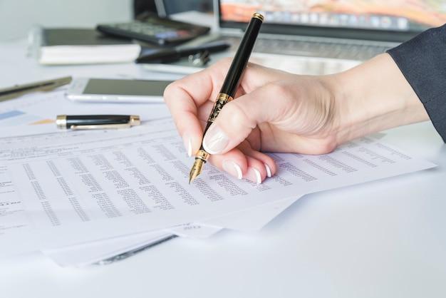 De holdingspen van de vrouwenhand bij bureau met documenten