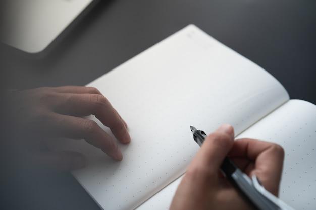 De holdingspen van de zakenman om op notitieboekjepagina te schrijven