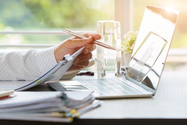 De holdingspen van de zakenmanhand voor het werken in stapels document dossiers die bedrijfsrapport zoeken