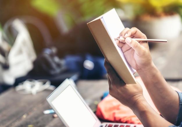 De holdingspotlood en notitieboekje van de mensenhand om aan het ontwerp te denken.