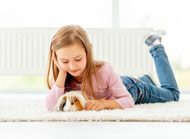 De holdingsproefkonijn van het meisje op de vloer