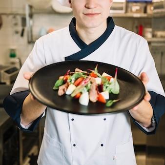 De holdingssalade van de kok met vlees op zwarte plaat