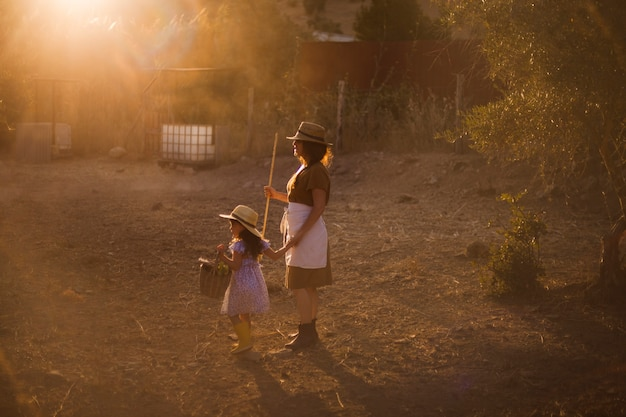 De holdingsstok die van de vrouw zich met haar dochter op het gebied bevindt