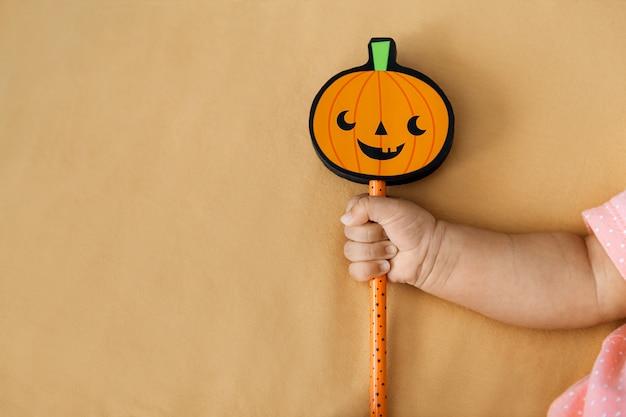 De holdingsstok van het babymeisje met pompoen op sinaasappel, copyspace aan de linkerkant