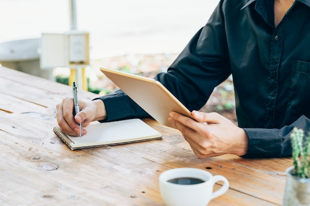 De holdingstablet van de bedrijfsmensenhand en het schrijven van notitieboekje in koffiewinkel.