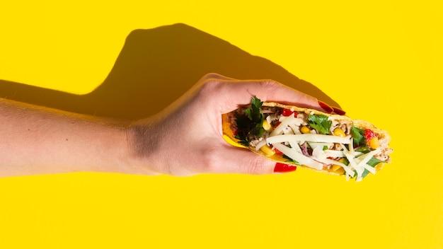 De holdingstaco van de close-upvrouw met gele achtergrond