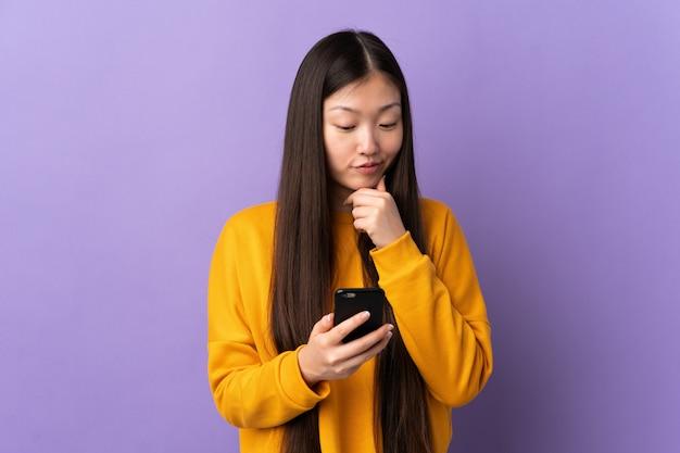 De holdingswafels van het tiener aziatische die meisje op beige muur worden geïsoleerd die twijfels hebben en met gezichtsuitdrukking verwarren