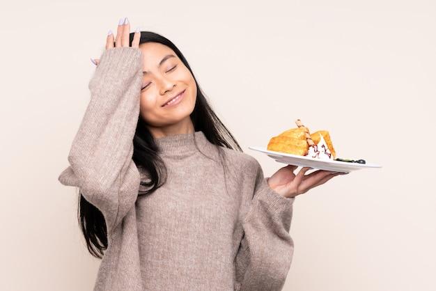 De holdingswafels van het tiener aziatische die meisje op beige muur worden geïsoleerd heeft iets gerealiseerd en de oplossing voornemens